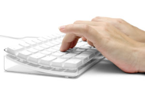 Female hands typing on a white  computer keyboard. White background.
