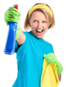 Young woman as a cleaning maid fiercely spraying liquid from blue sprayer, isolated over white