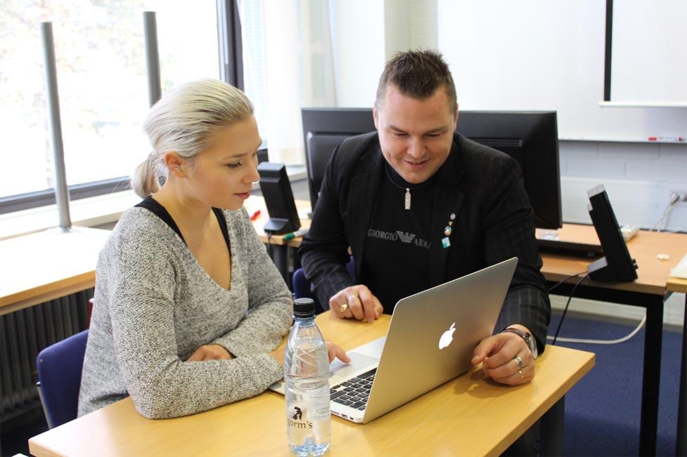 Juha Ahola opastaa koulutettavaa tietokoneen näytöltä